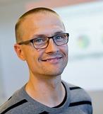 Porträtt på leende Patrik Haraldsson med glasögon