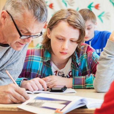Lärare med grått hår sitter bredvid elever och tittar i arbetsbok