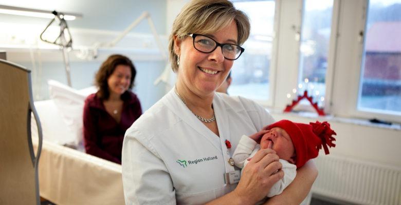 Barnmorska Annika Neij håller nyfödd bebis med röd mössa, tema jul på jobbet