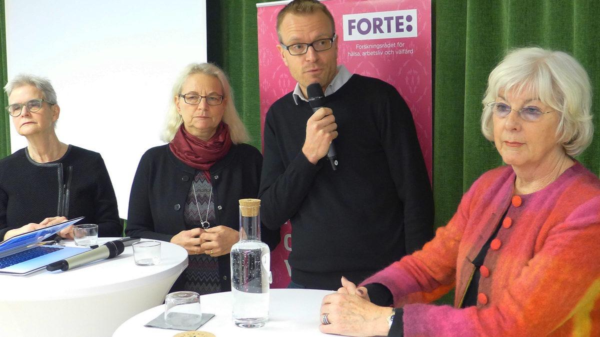 tre kvinnor och en man vid ståbord. manen håller i en mikrofon och ser på en av kvinnorna.