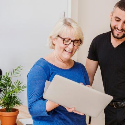 en kvinna och en man står lutade mot ett skrivbord och ler och tittar i ett papper tillsammans.