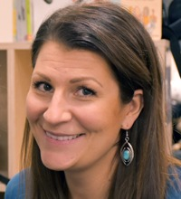 Porträtt av lång- och mörkhårig leende Malin Enström, pratar Vår arbetsmiljö