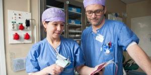 Kvinna sjuksköterska håller i blodpåse och scanningsapparat, kollega man sjuksköterska står bredvid, Arbetsmiljölyftet
