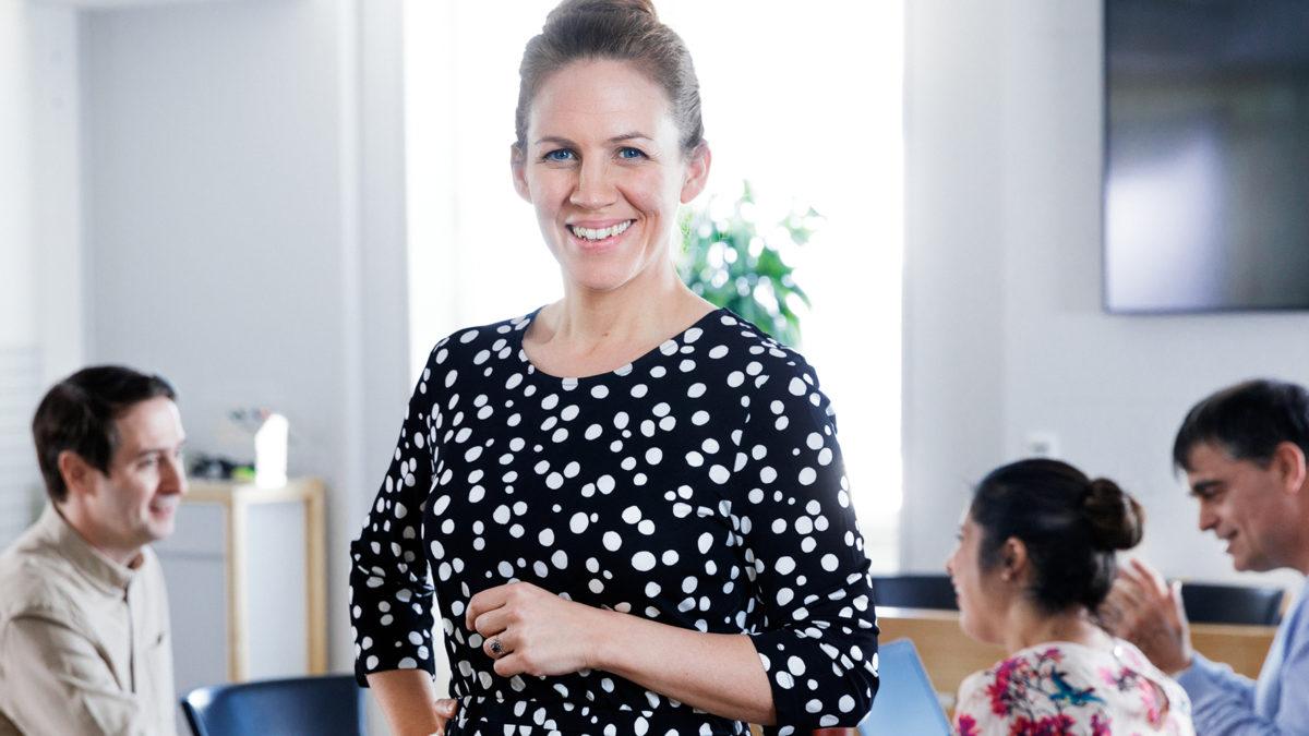 Glad kvinna i medelåldern, prickig blus, och uppsatt hår, står upp framför en sittande grupp arbetskamrater vid ett mötesbord.
