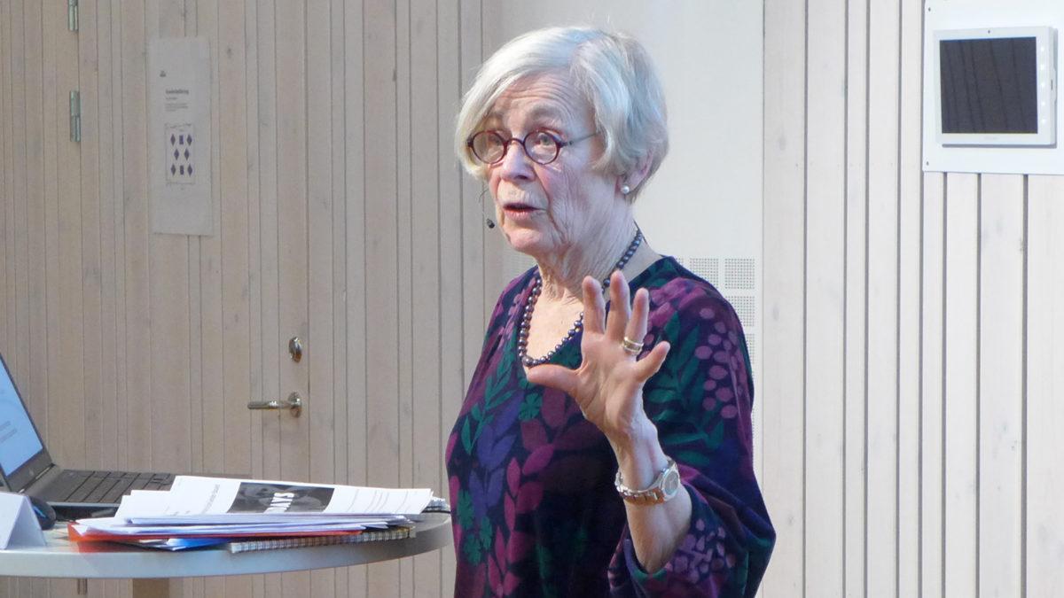 halvbild på kvinna, grått hår, lila tröja, som pratar inför publik man inte ser. ena handen höjd iför att förstärka något hon sagt.