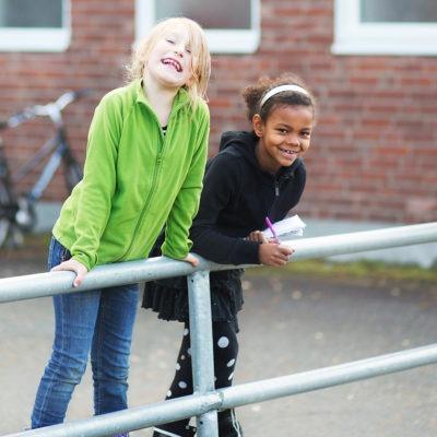 Två glada lågstadiebarn lutar sig mot ett räcke på en skolgård.