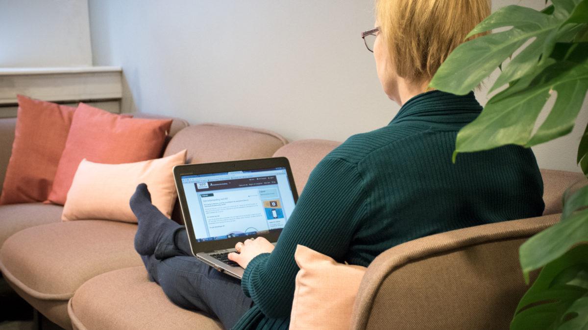 Kvinna sitter i soffa med laptop i knät, webbterapi