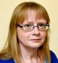Porträtt Carina Lenngren med glasögon, ljus bakgrund, Arbetsmiljölyftet