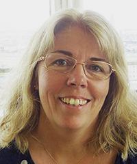 Närbild av leende kvinna med blont långt hår och glasögon.