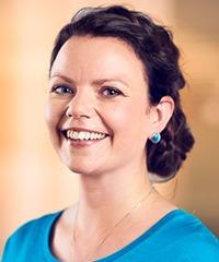 porträtt på kvinna som ler, blå tröja och blå örhänge, uppsatt mörkt hår.