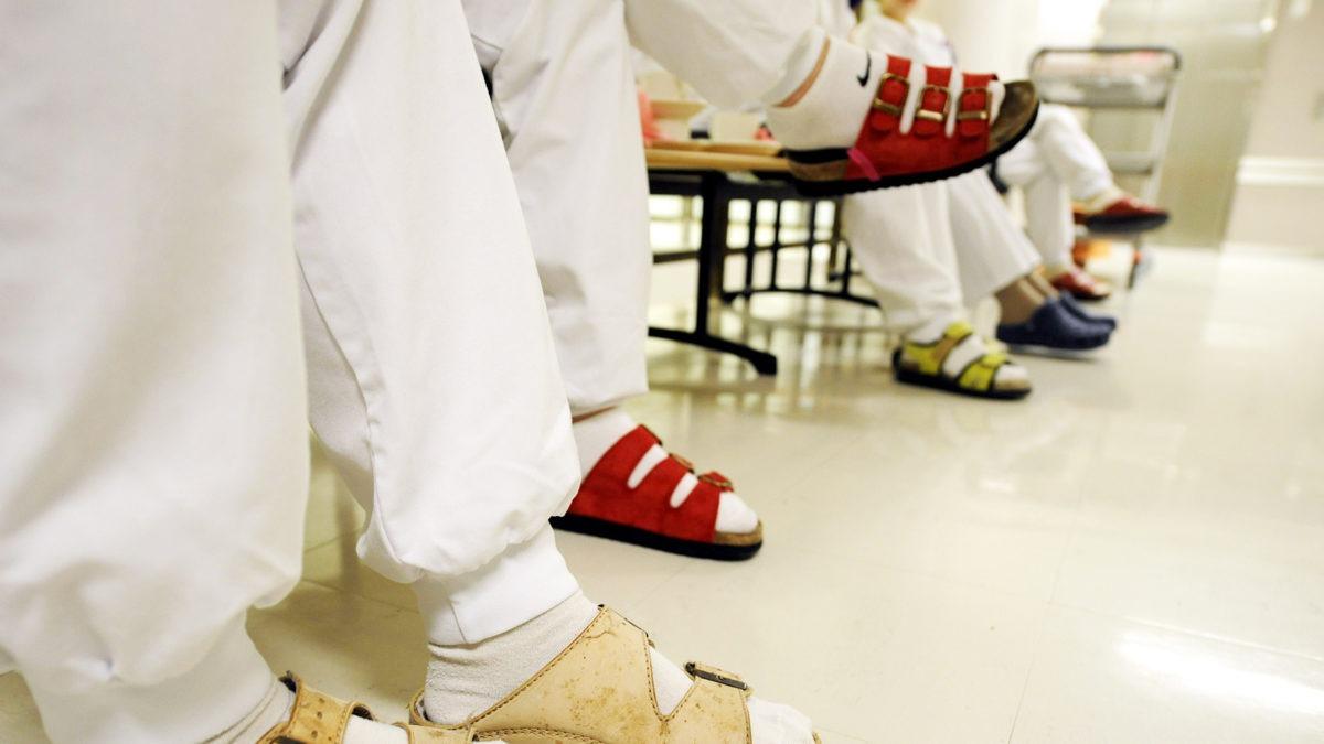 närbild på fem, sex toffelbeklädda fötter, vars ägares itter på rad på ett par stolar i något som kan vara ne sjukhuskorridor. Benen ovan fötterna har sjukvårdskläder.