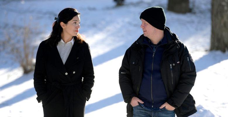En kvinna och en man promenerar utomhus i snö, vända mot kameran.