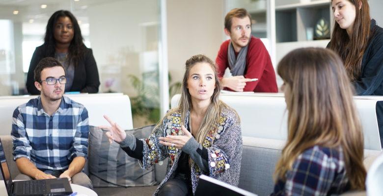 Sex män och kvinnor i samtal vid bord, tre sitter, tre står, laptop på bordet, dela-kultur