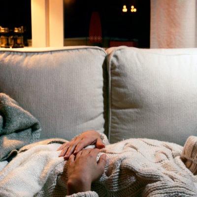 Kvinna sover i soffa med vita kuddar och grå filt. Fönster i bakgrunden med mörk natt utanför. Till artikel om dygnsvila.