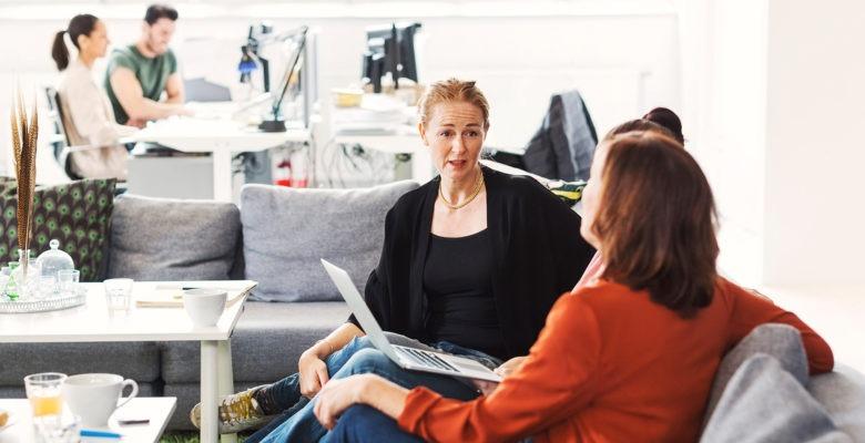 Två kvinnor sitter i en soffa på ett kontor och pratar. En med ansiktet mot kameran, en i profil.