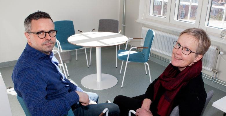 en man och en kvinna sitter på varsin stol i ett ganska kalt rum, med ett bord längre bort. Vackert upplyst av solen.