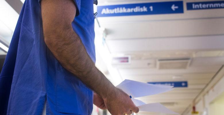 en sjukhuskorridor med skylt i taket som hänvisar till aktuläkardisk. En person i blå vårdkläder står i förgrunden, bara bålen syns. Artikel om skiftarbete.