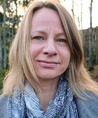 närporträtt på Caorlina Bigert, som ser in i kameran. Blont långt hår och ljusblå sjal runt halsen. Bilden tagen utomhus med skog i bakgrunden.