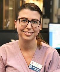 närbild på leende kvinna i rosa vårdkläder. Brunt uppsatt hår och glasögon.