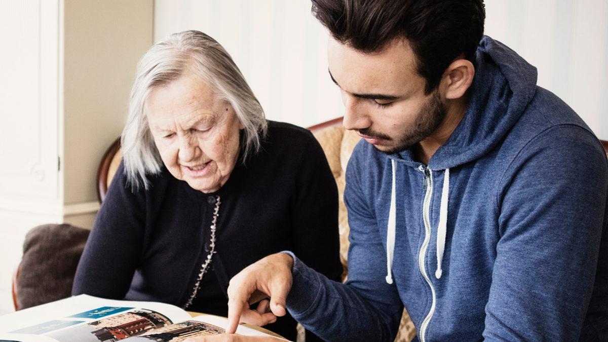 En äldre kvinna och en ung man sitter tillsammans vid ett bord och tittar i en bok.