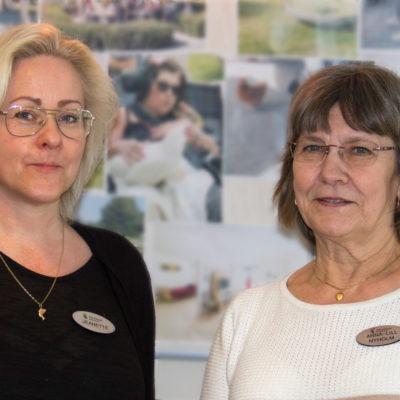 Halvporträtt två kvinnor framför vägg med bilder, arbetsmiljöutbildningen