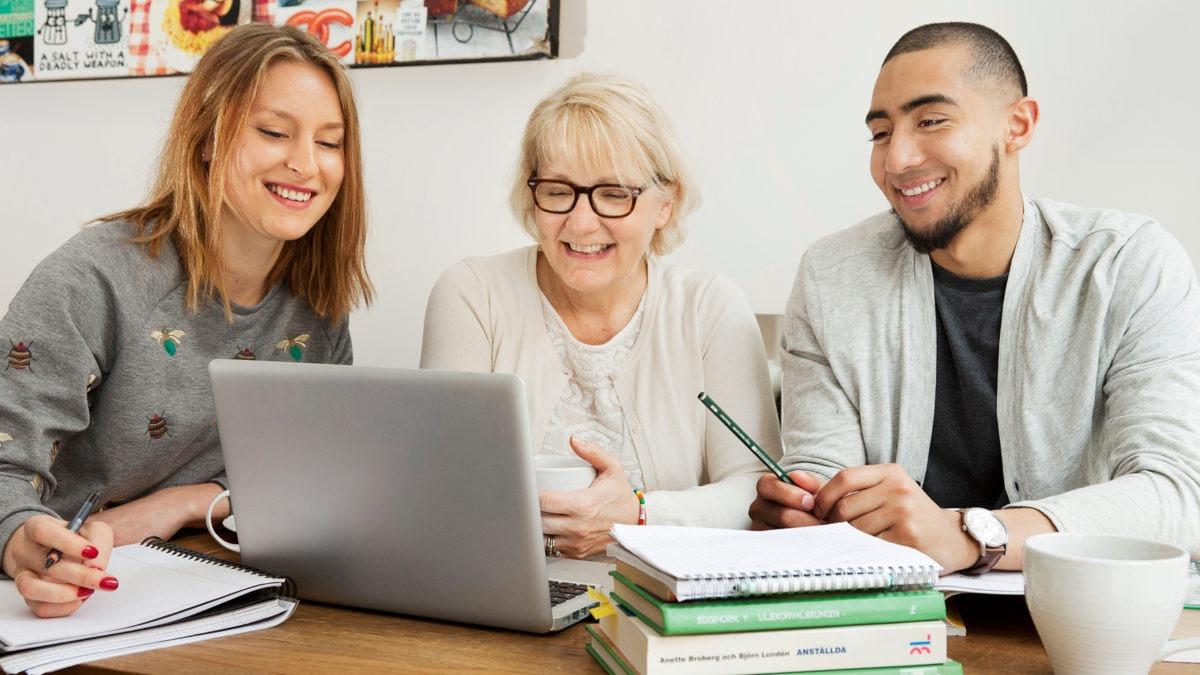 Tre glada personer två kvinnor en man sittande vid bord med dator och böcker