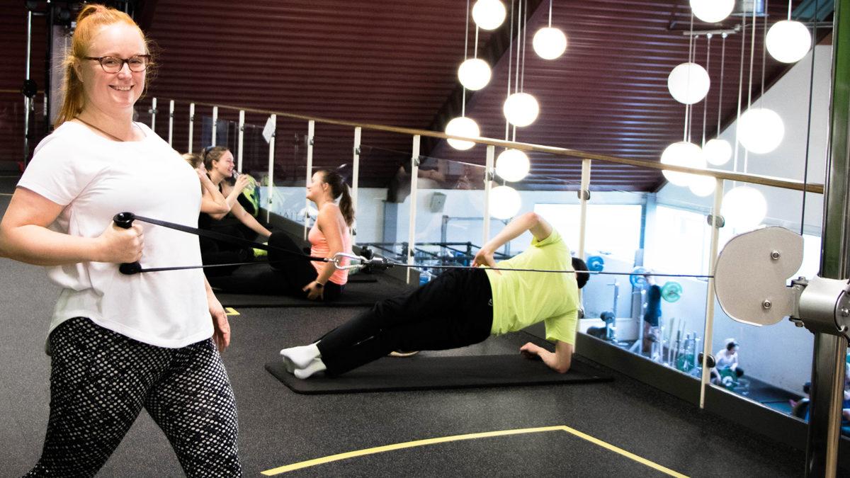 kvinna i vit tröja på träningslokal drar i töjbart rep. I bakgrunden ett par personer som gör träningsrörelser på golvet i liggande läge.