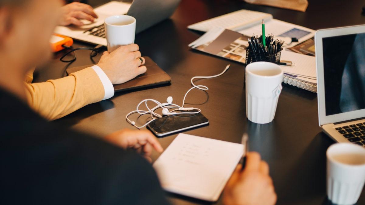 Bild på ett bord med anteckningsblock, kaffemuggar, någon del av en dator. Ett par personers händer och armar syns, inga ansikten.