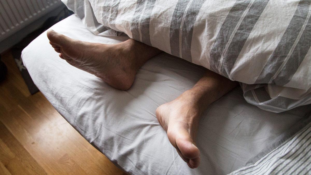 två fötter sticker ut under ett täcke vid fotändan av en säng.