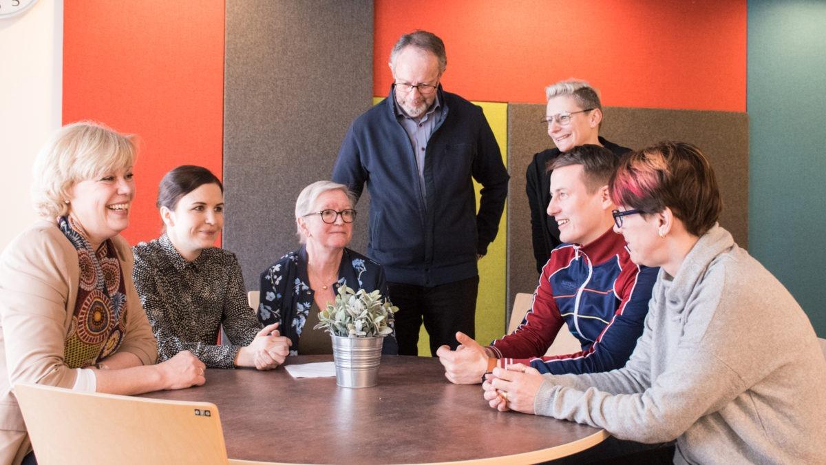 Sju glada personer runt ett bord, delaktighet Uppsala socialtjänst