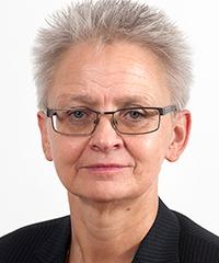 närbild på kvinna i grått kortklippt hår som står rakt upp från huvudet.