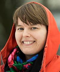 närbild på glad kvinna med orange kapuschong över huvudet, utomhus.