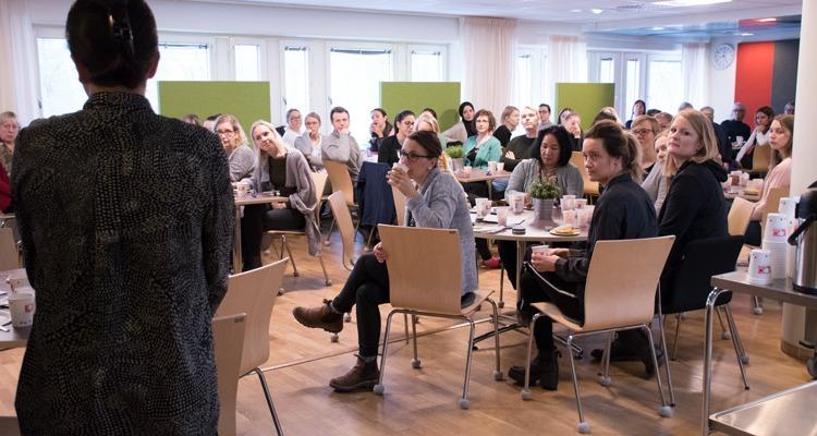 Socialsekreterare runt runda bord lyssnar på talare till vänster i bild
