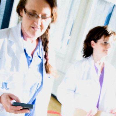 Två kvinnliga vårdanställda, klädda i vita rockar, går snabbt i en sjukhuskorridor. Rörelseoskärpa i bilden.