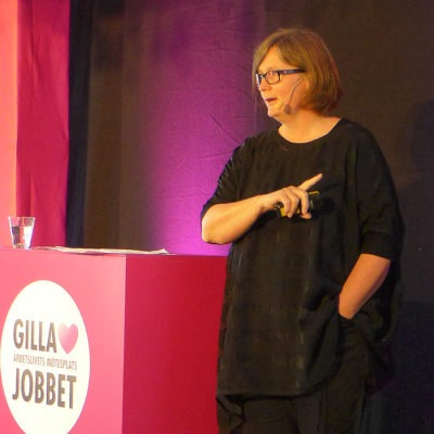 Lisbeth Rydén håller föredrag på Gilla jobbet. svart klänning, lila bakgrund.