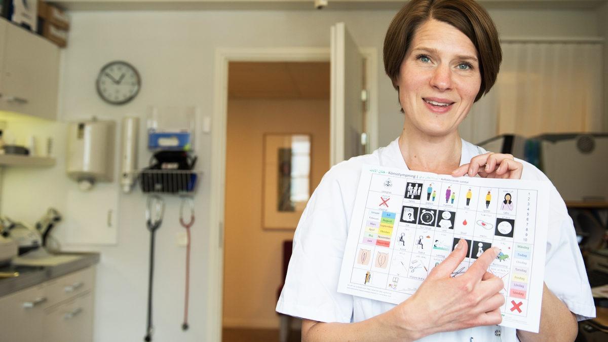 barnmorska i arbetskläder står i mottagningsrum och håller upp ett bildstöd , en karta med bilder..