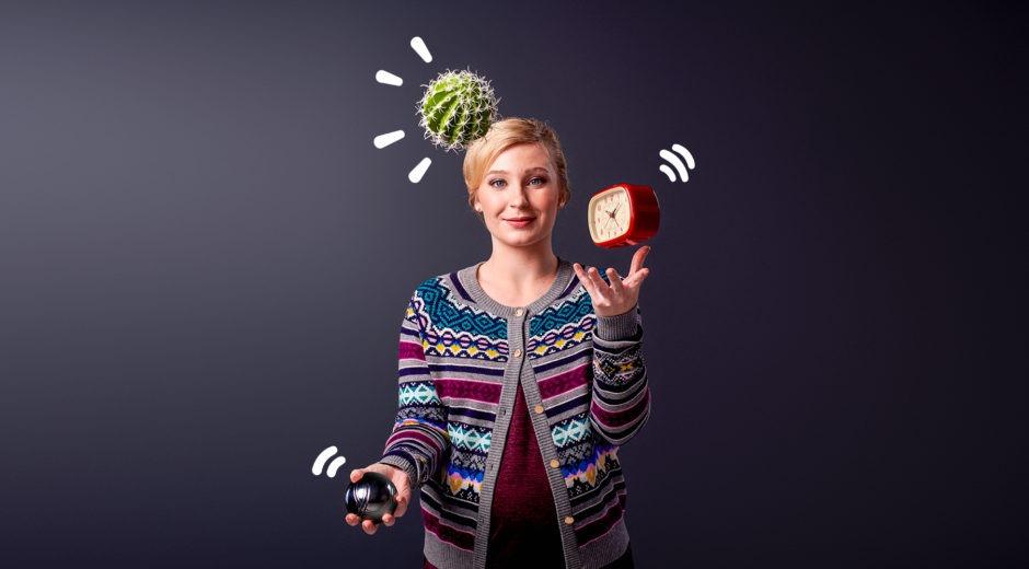 Kvinna jonglerar med lätthet en klocka, en kaktus och ett tungt klot