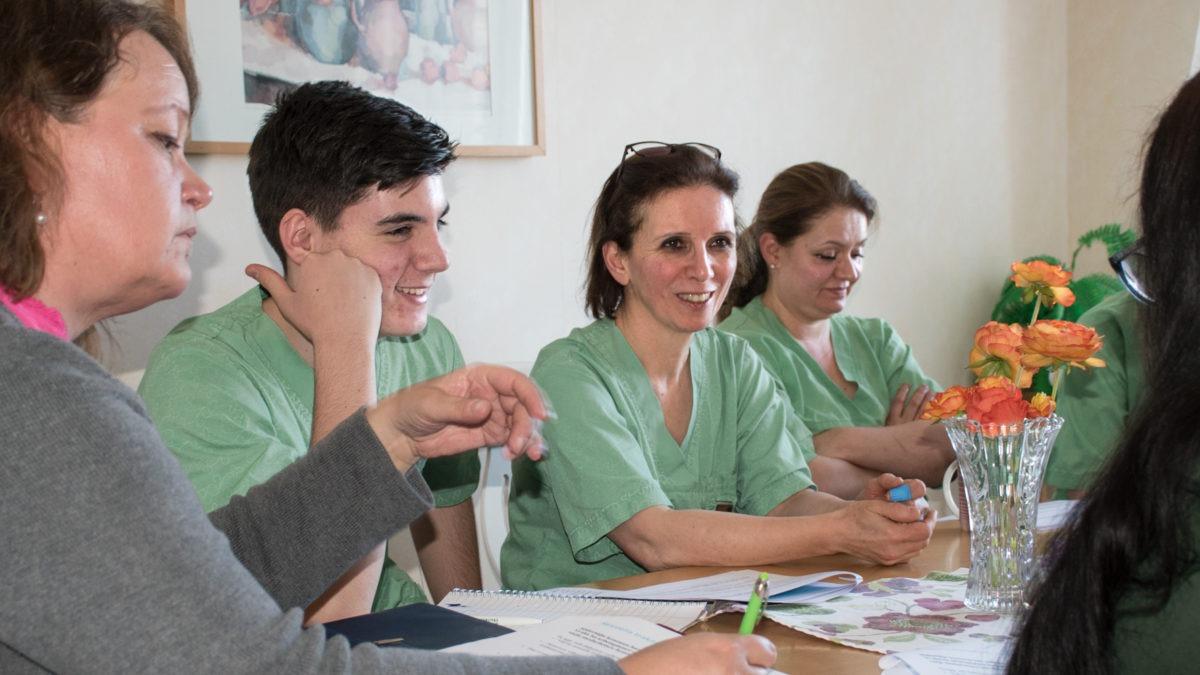 Flera personer i gröna kläder diskuterar sittande vid ett bord, arbetsplatsträff