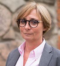 proträtt på Eva Schömer, forskare. Blont hår i page, svarta glasögon, grå kavaj, rosa skjorta.