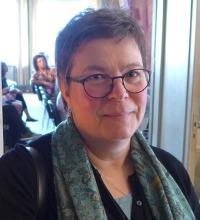 närbild av medelålders kvinna med grön sjal och glasögon.