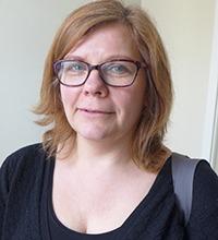 närbild på leende kvinna i medelåldern, i svart tröja och glasögon.