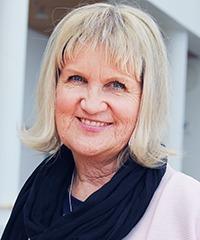 ärbild på glad kvinna i blond pagefrisyr, svart halsduk och rosa tröja.
