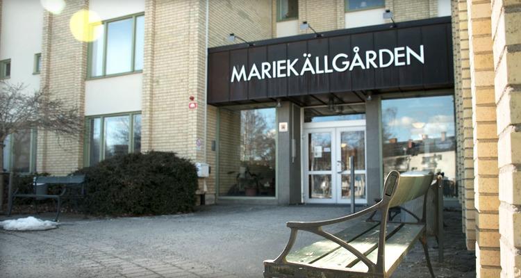 Gul tegelfasad med ingång Mariekällgården