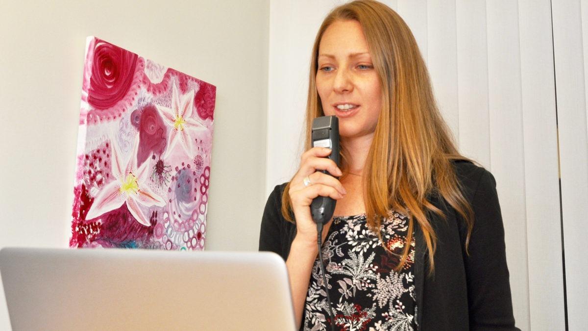 Ann Granström Thalberg står upp och pratar i en taligenkänning framför datorn.