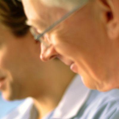 närbild av två leende män i profil, i vårdkläder. En av dem lite äldre.