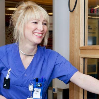 generebild en glad kvinna i vårdkläder öppnar en dörr