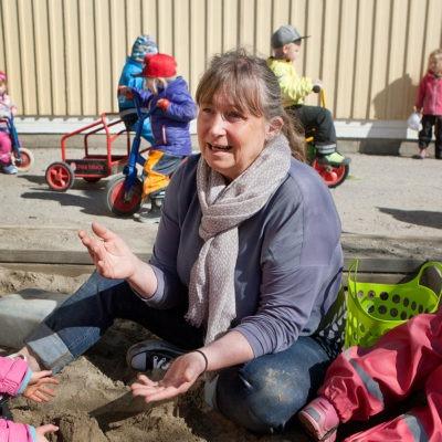lena berggren förskollärare i Sundsvall, sitter i en sandlåda tillsammans med förskolebarn