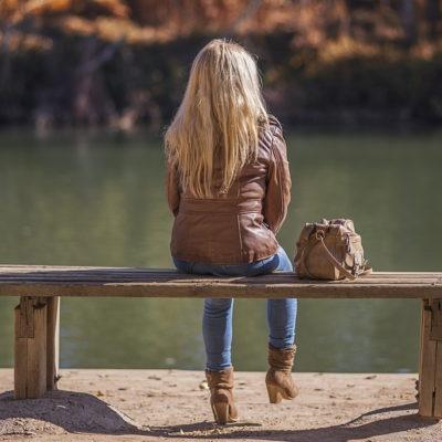 bild av kvinna sedd bakifrån, sittande på soffa utomhus vid sjö i höstlikt landskap.