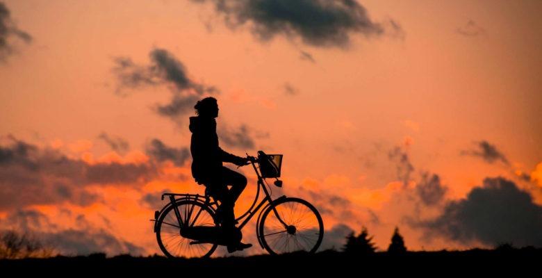 Cyklist i solnedgång har sund levnadsvana som kan mätas i arbetshälsoekonomiskt analysverktyg.