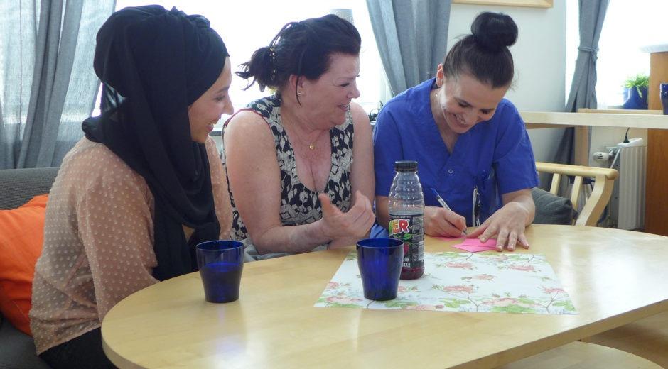 Arbetsplatsträff. Tre kvinnor sitter i en soffa och skriver lappar tillsammans.